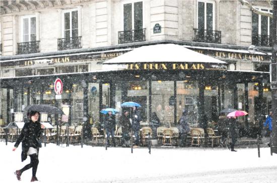 A woman walks past a cafe in Paris. © Dipankar Paul/FoloMojo